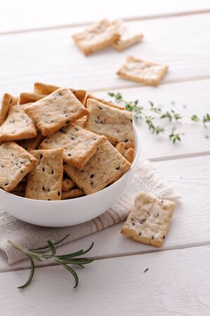 crackers: crackers with herbs and black sesame seeds on white wooden table Stock Photo