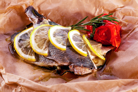 daurade: baked fish close-up decorated with lemon and rosemary served on parchment paper Stock Photo