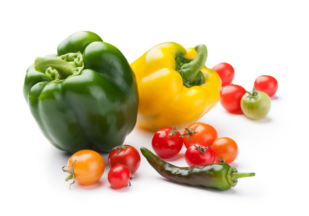 bell peppers: first crop of fresh vegetables bell peppers, cherry tomatoes and chili close-up isolated on white background Stock Photo