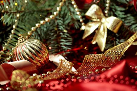 christmas tree ball: New Year holiday background with golden ball close-up,   ribbons, beads and bow  on Christmas tree