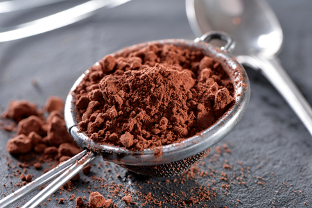 cocoa powder close-up with sieve and silver spoon on black slate plate