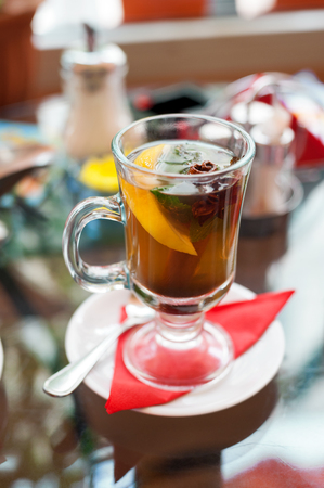 glass of tea with lemon, cinnamon sticks, anise star and mint  mint leaves on table in cafe Stock Photo