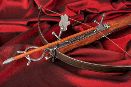 retro stylized wooden crossbow  close-up on crimson silk background
