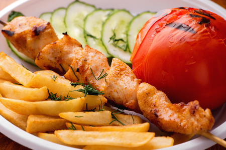 appetizing chicken kebab, fried potatoes chips,  grilled tomato and fresh sliced cucumbers close-up on white plate Stock Photo