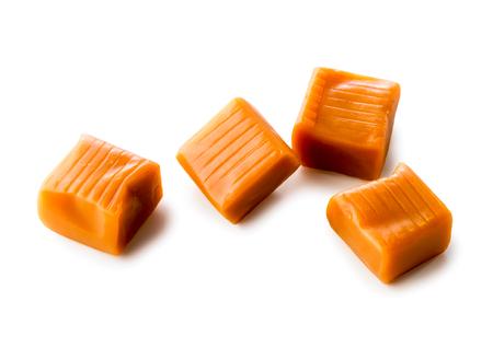 kompozycja czterech karmelowych cukierków z bliska na białym tle (ze ścieżką przycinającą)
