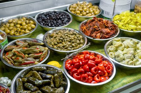 salad bar with cold snacks marinated olives, peppers and mushrooms in metal bowls