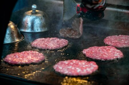 roasting raw marbled beef burger patties on  iron grill  outdoors