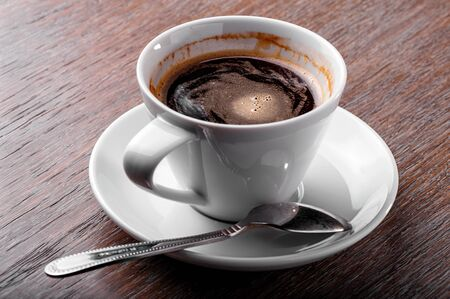 white porcelain cup of coffee close-up with spoon and saucer  on  wooden background 写真素材
