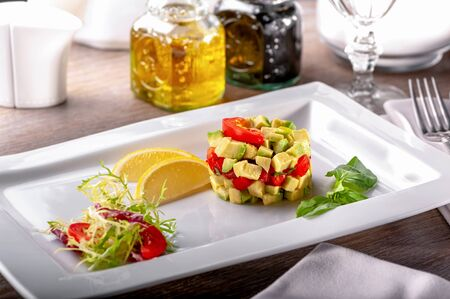 restaurant table with dish of cold appetizers tomato and avocado salad with arugula leaves, basil, lemon slices, fork on napkin, glass, gravy boats