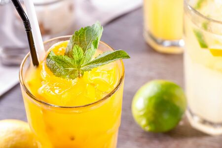 glass of lemonade close-up with ice, leaf of mint and plastic straw on  table next to citrus fruits Imagens