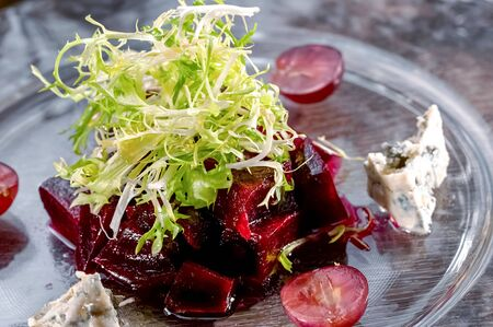 gourmet beet and blue cheese salad close-up garnished with arugula leaves and chopped cherry tomatoes on glass dish