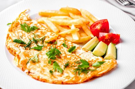 egg omelet with fried potatoes, fresh vegetables, green dill and parsley close-up on white plate Archivio Fotografico