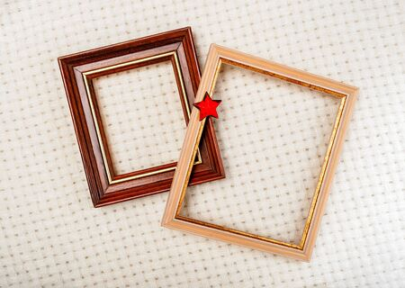 picture frames with gilding and red star close-up on white woolen plaid background Christmas decoration