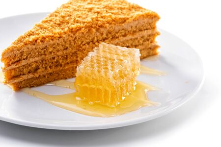 piece of honeycomb close-up next to piece of honey cream cake on porcelain plate against white background