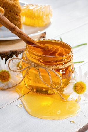 small glass jar of honey with dipper inside close-up, chamomile flowers and plate of cake on white wooden background
