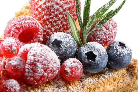 fresh raspberries, cranberries, blueberries and strawberry sprinkled with icing sugar close-up on fruit cream cake top with rosemary leaves isolated on white background
