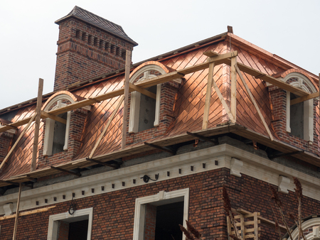 The builders made an unusual copper-colored roof with a new building under construction Foto de archivo