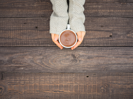 On a wooden table, well-groomed womens hands hold a mug of hot cocoa