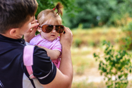 Amazing little girl is playing with sunglasses with her father