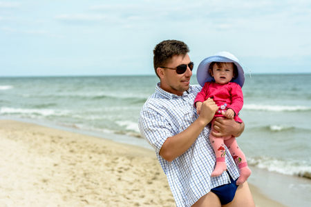 A young father holds his daughters hands on the beach Zdjęcie Seryjne
