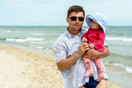 A young father holds on his hands a wonderful little girl in the beach on a blue hat and a red dress Zdjęcie Seryjne