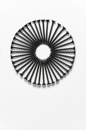 Photoset patterns arranged from black screws isolated on a white background in the form of a circle and a heart