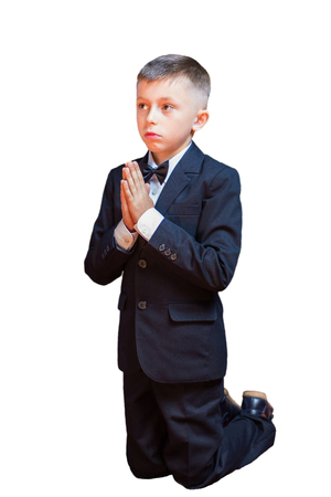 A little boy in a suit praying, isolated on a white background. Traditionally, children take the first communion in the church