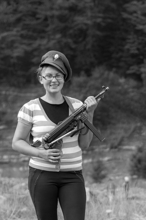 A beautiful woman wearing a hat holds a trophy weapon
