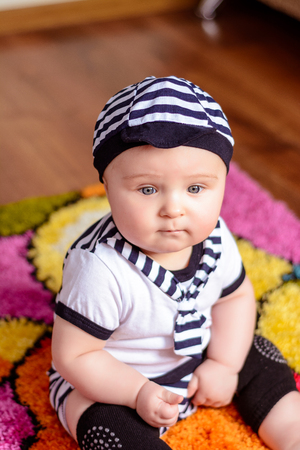 A pretty baby in a striped shirt and hats seated on the mat in the room 2018