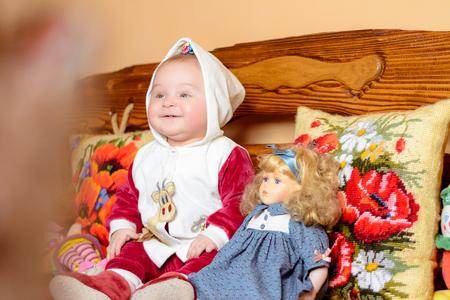 Un niño pequeño en un chal sentado en un sofá con almohadas bordadas 2018 Foto de archivo