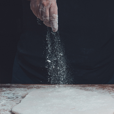 An old woman's grandmother is kneading a dough for the preparation of bread on a black background