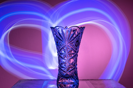 The Crystal Vase On A Red Background Is Illuminated With Rays