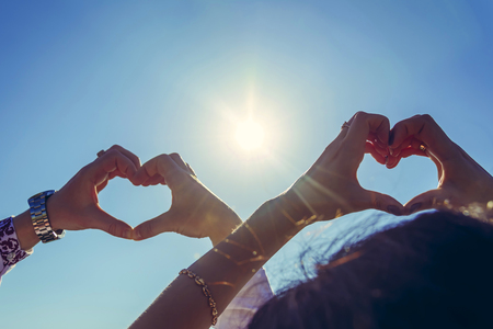 Newlyweds hold their hands in the shape of a heart against the background of the sunny sky