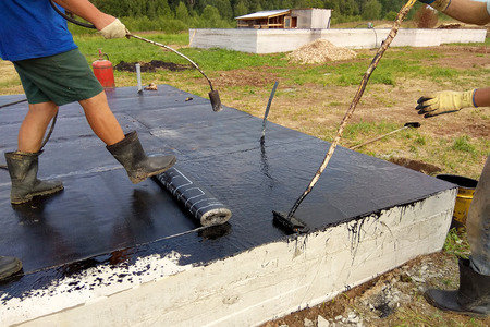 Professional installation of waterproofing on the concrete foundation Two worker at construction site.