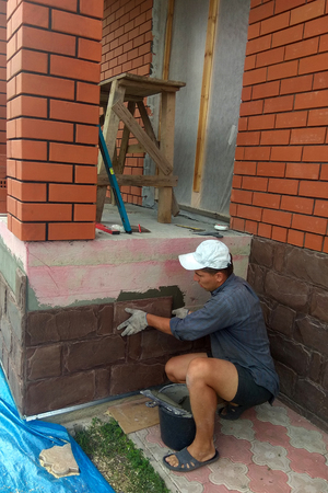 gluing a granite stone on the foundation of the building facing 2018