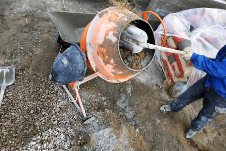 auxiliary worker uses a shovel to prepare a cement mortar on a construction site 2018