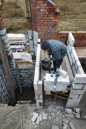 The master, using a trowel, glues gasblocks with a glutinous solution at the construction site 2018 免版税图像