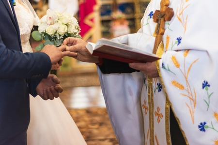 the priest pulls the wedding ring to the bridegroom 2019 Foto de archivo