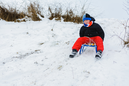 for a sledge down the boy in red pants is very happy 2019 版權商用圖片