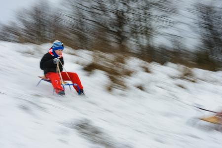chłopiec zjeżdża na sankach ze wzgórz, ruch jest zamazany 2019