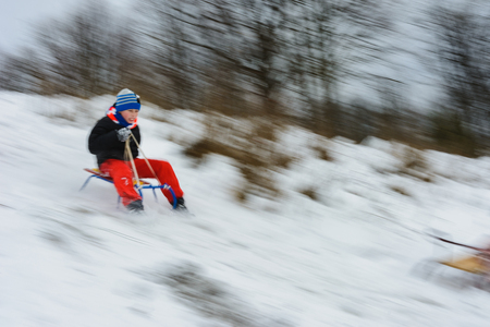 el niño desciende de las colinas en el trineo, el movimiento se desdibuja 2019