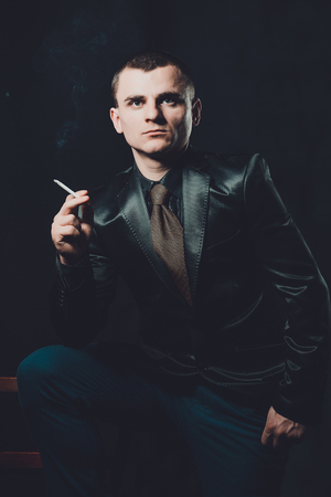 a young man smokes a cigarette, a black background, a classic black suit 2019 Stock Photo
