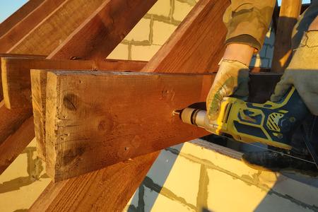 El trabajador utiliza un taladro en la construcción del techo 2019 Foto de archivo