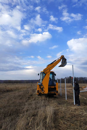 The excavator with a bucket pushes the pillars on the fence in the field near the house 2019