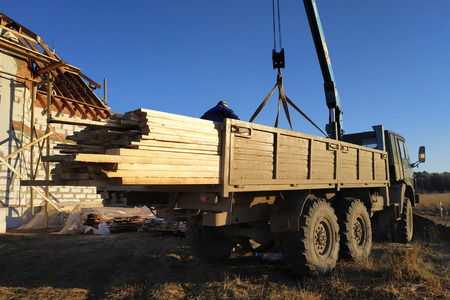Unloading boards from the side of the crane with the help of people 2019