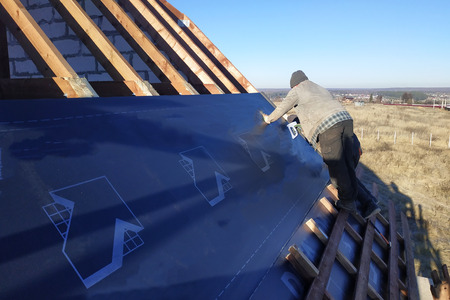 Workers on the roof of the house install a waterproof film under the roof and secure it with a stapler 2019