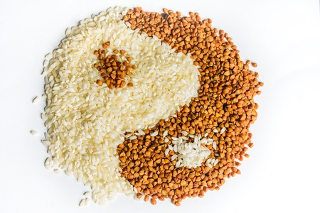 The symbol of yin yang is laid out of buckwheat and rice, texture. 2019
