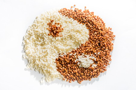 The symbol of yin yang is laid out of buckwheat and rice, texture. 2019 Archivio Fotografico - 119238558