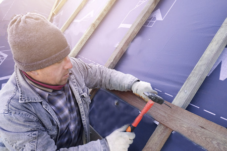 The master clogs the nail into a beam, fixing this gidrorizer to the rafters 2019 Stock Photo