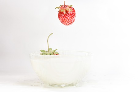 Splashes of milk from falling strawberries, white background. 2019 Stock fotó